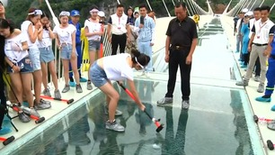 Her forsøker de å knuse glassbroen de står på